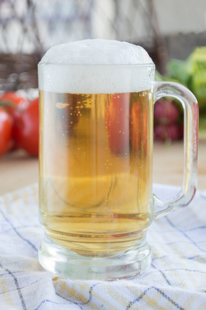 Glass of beer on plaid dishcloth with vegetables in background