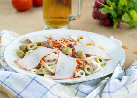 Pasta with ham ketchup and olives on white plate