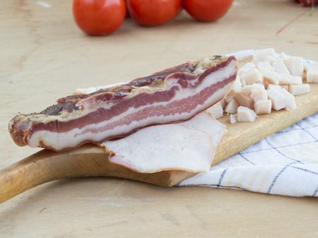 pancetta cubetti: Pancetta e prosciutto sul tagliere con pomodoro in background Archivio Fotografico