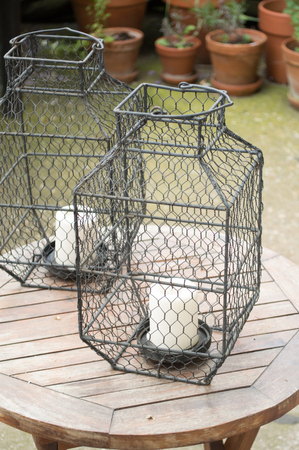 Candles in cages on wooden table as decorative detail in garden Stock Photo