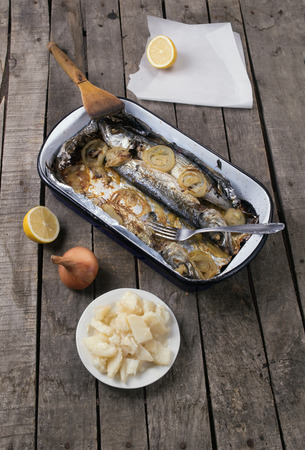 just cooked  mackerel fish with potato salad, onion and lemon on gray wooden background. Stock Photo