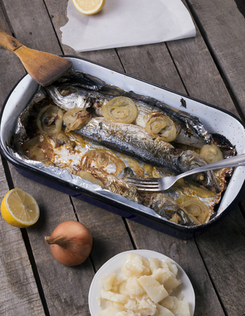 Cooked  mackerel fish with potato salad, onion and lemon on gray wooden background, close up