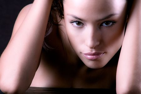 leaned: attractive woman with hands leaned on table, studio shot on dark background