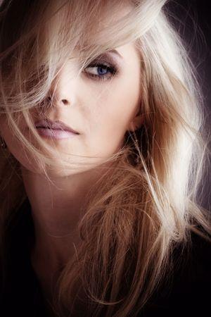 depress: blond woman portrait in dark, hair over face