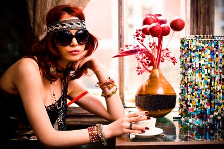 young woman in summer clothes and sunglasses drinking coffee in a restaurant photo