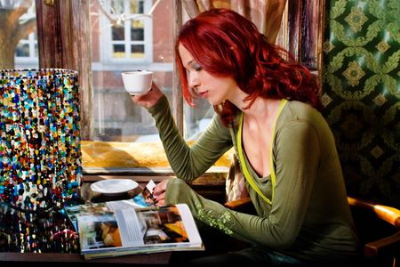 red hair woman drinking coffee and reading magazine in cafe photo