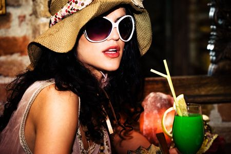 young woman with hat and sunglasses drinking cocktal