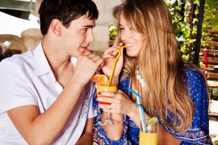 young couple in love drinking juice, outdoor shot photo