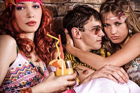 two young women and man on a party flirting photo