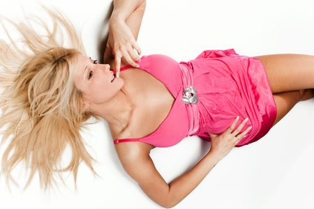 pretty blond woman in pink dress laying, studio white background photo