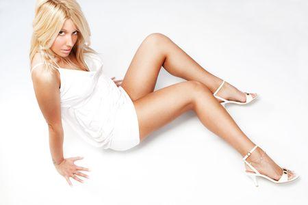 piernas con tacones: mujer guapa rubia de vestido blanco y zapatos de tac�n alto sentado en el piso