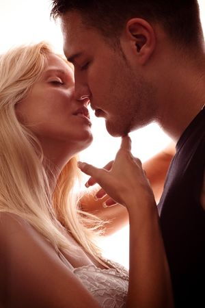 erotic woman: young couple in love, kissing, studio shot, back light Stock Photo