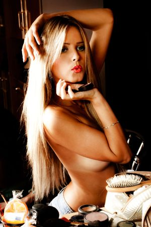 sensual blond woman in front mirror with make up accessories, indoor shot photo