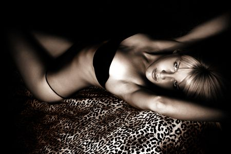 sensual blond in lingerie lying in bed, indoor shot