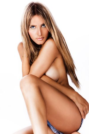 bronzed: attractive tanned blond woman sitting on floor, studio white Stock Photo