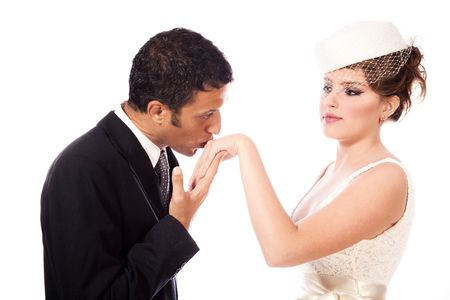 mixed marriage:  groom kissing brides hand, studio shot white background