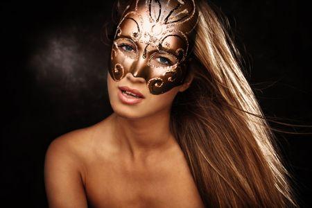 beautiful blond woman with mask portrait, studio dark background photo