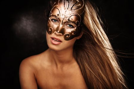 mystery woman:  beautiful blond woman with mask portrait, studio dark background