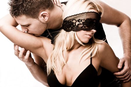 erotic couple: young masked couple in love, studio shot on white