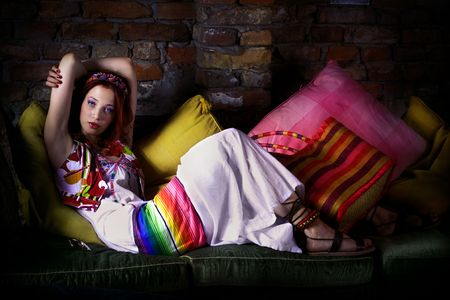 red hair woman in oriental clothes resting on sofa Stock Photo - 5773507