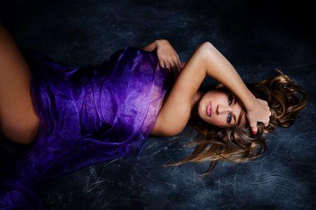 lascivious: sensual blond woman enclosed in purple silky veil, studio shot