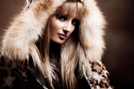 young blond woman in winter fur clothes, studio shot photo