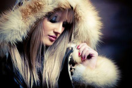 beautiful young blond woman in fur, studio shot photo