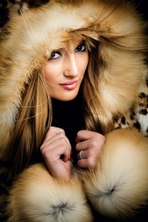 pretty blond woman portrait in fur clothes, studio shot photo