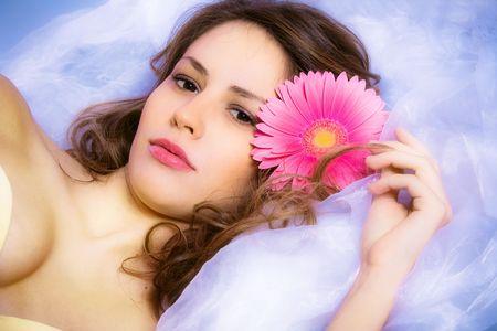 young brunette woman with flower, beauty portrait, studio shot photo