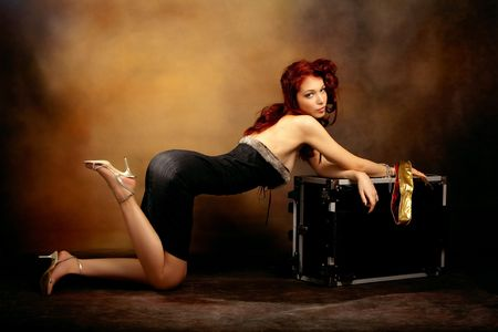 nude art model: beautiful red hair woman in sexy dress leaned on trunk, studio shot