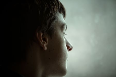 окружающей среды: teen boy portrait by the window, ambient light, selective focus