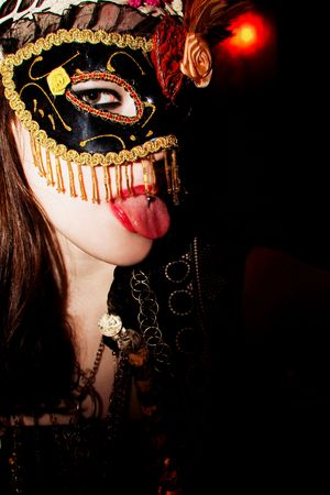 young woman wearing mask showing tongue photo