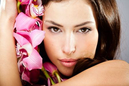 sensual brunette woman beauty portrait with orchid photo