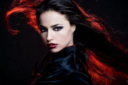 wild hair: capelli scuri bella donna con i capelli in movimento e la luce rossa posteriore  Archivio Fotografico