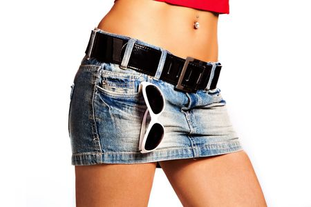 women in jeans: tanned woman body in short jeans skirt with sunglasses in pocket, studio white
