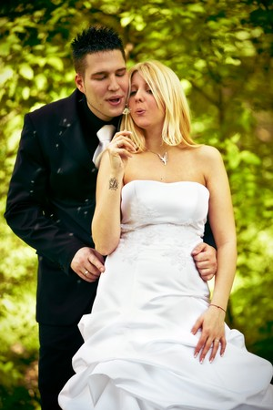 blowball: happy bride and groom blowing blowball outdoor shot
