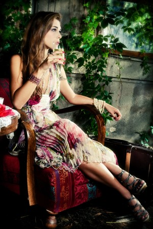 outdoor glamour: beautiful young elegant  woman drinking champagne in garden