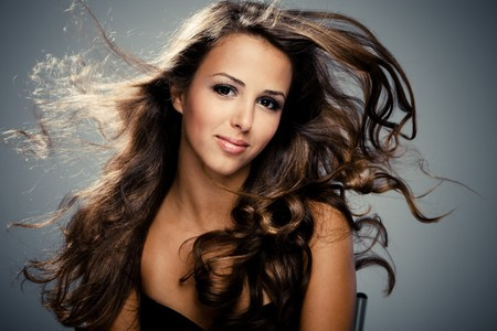 young brunette  woman with long flying hair, studio shot photo
