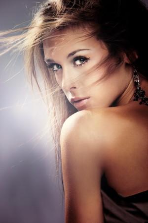 beauty portrait of young brunette woman, hair fly, studio shot photo