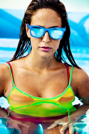 attractive young woman in swimming pool wearing sunglasses Stock Photo