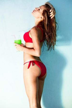 jugo verde: disfrutar de una mujer joven en bikini sosteniendo el vaso de zumo de sol