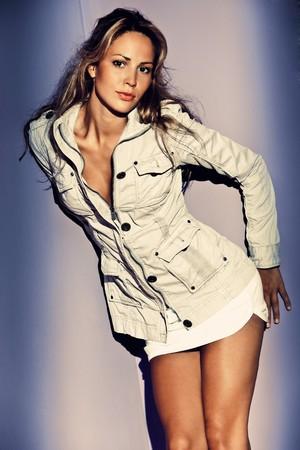 falda corta: joven mujer Morena en falda corto y chaqueta, interior disparo  Foto de archivo