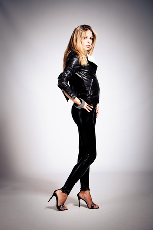 young blond woman in black leather, studio shot photo