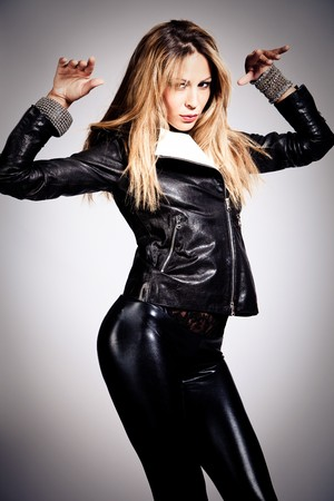 catsuit: young blond woman in black leather, studio shot