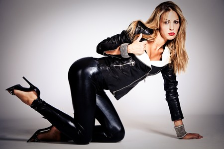 young blond woman in black leather, studio shot Stock Photo - 7832550