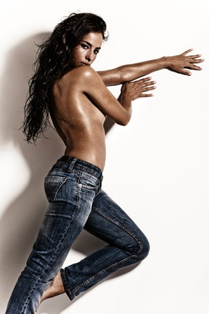 attractive brunette in blue jeans against white wall photo