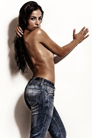 nude woman standing: attractive brunette in blue jeans against white wall