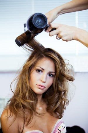 hairdryer: young woman grooming, indoor shot available light Stock Photo