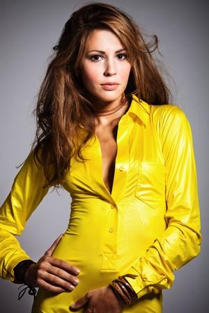 young brunette woman wearing yellow shirt , vertical orientation, studio shot Stock Photo - 8005305