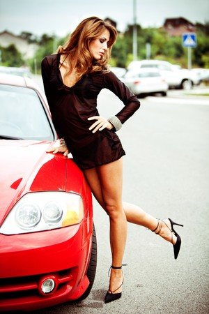 pretty woman in black transparent dress rest upon red car, outdoor shot photo